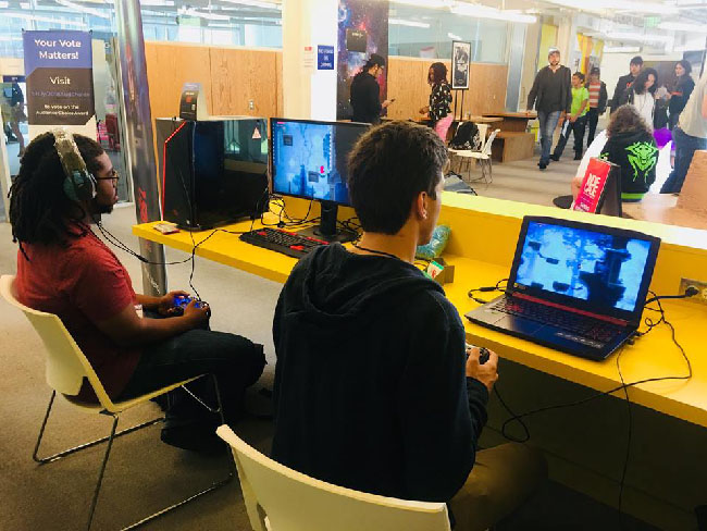 "Two people playing a demo of ""Balam and the Spirit Within"" on two computers, in the yellow rooms of the Santa Monica College Center for Media and Design."