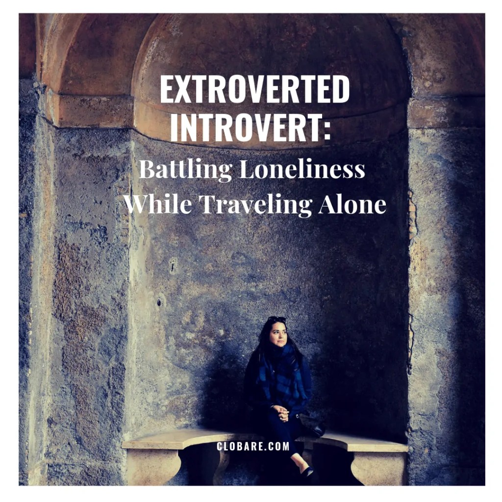 "Words that say ""Extroverted Introvert: Battling Loneliness While Traveling Alone"". Image of Clo Bare sitting in a stone archway."