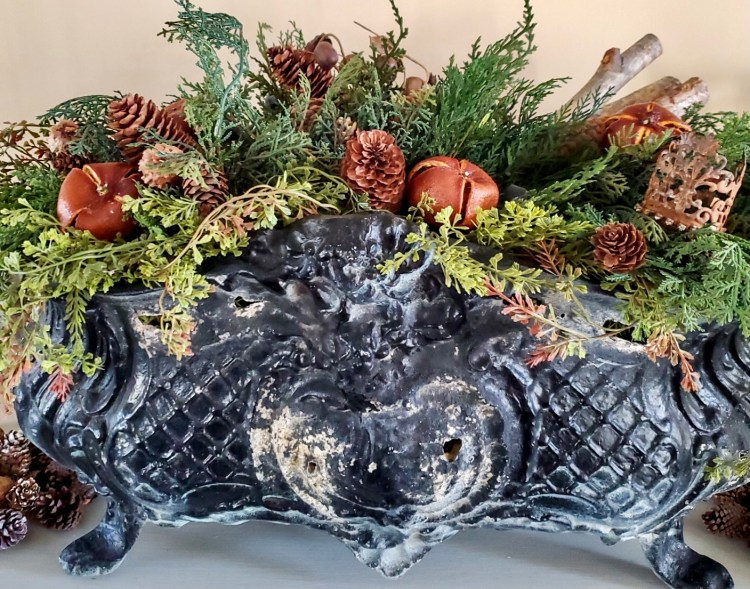 Close up of a Jardinière filled with greens and dried oranges, and pine cones