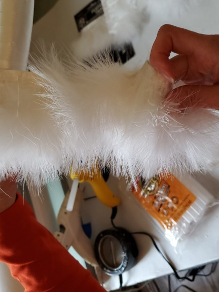 Wrapping the fur trim with satin over the wreath