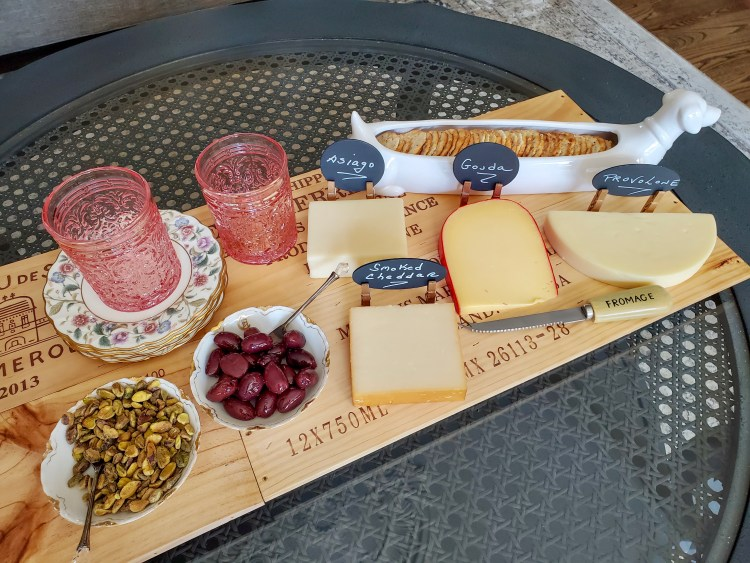 another look at the charcuterie board with the cheese markers, glasses in pink, floral dishes.  Olives and pistachios in bowls with crackers in a Dachshund cracker holder