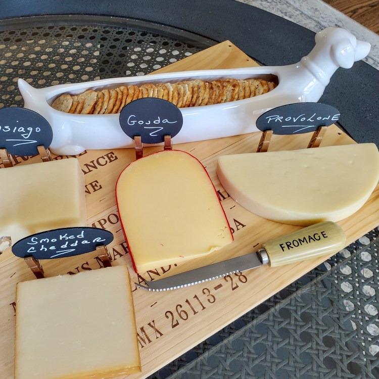 four cheese markers with smoked cheddar, provolone, gouda and asiago written on them on the charcruterie board with crackers in a Dachshund cracker holder