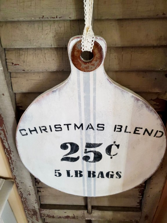 Christmas signs with a rusted washer.  Hanging from a shutter