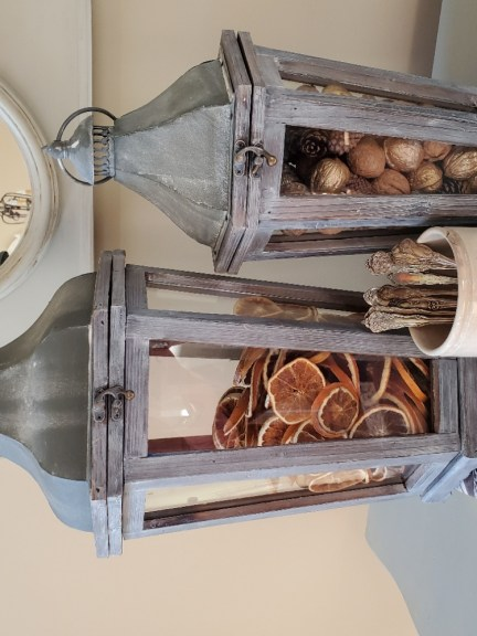 large lantern flled with dried orange slices on top of a book.   Smaller lantern flled with walnuts and pinecones.  White crock filled with silverware with walnuts next to it