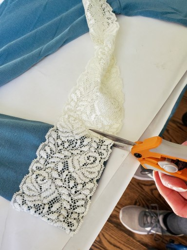 lace getting cut to add to the bottom of the T-shirt arms