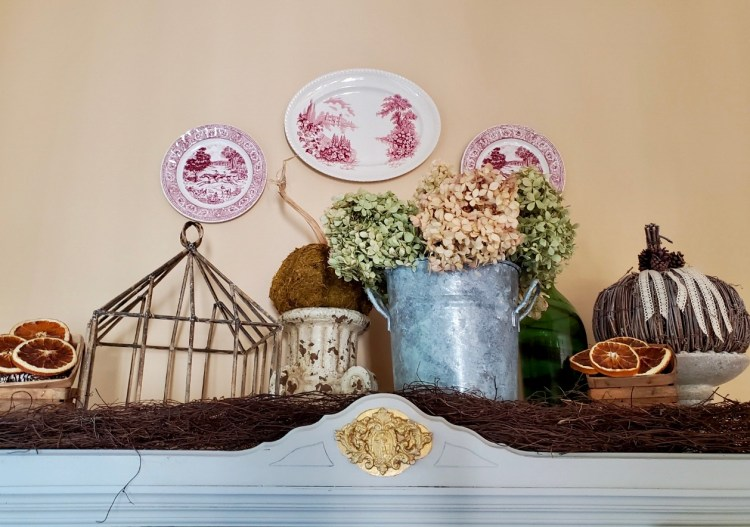 Top of hutch showing natural fall decor.  Pumpkins, dried hydrangeas, red transferware hanging on the wall