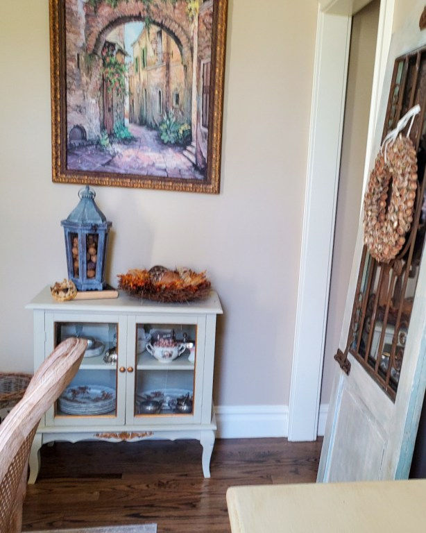 a picture of a small china cabinety and a lantern and wreath for natural fall decor