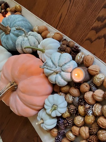 an angled shot of the chalk painted pumpkins with candles, walnuts and pinecones