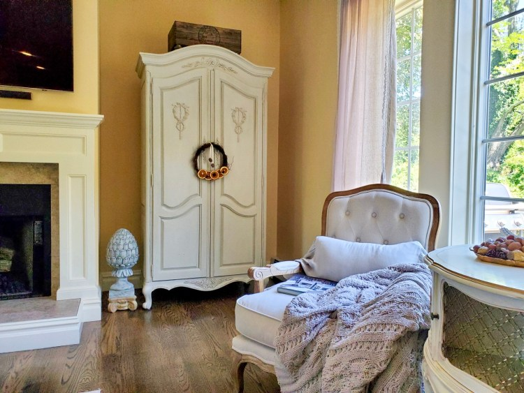 French armoire and one chair and heavy throw blanket in this picture of natural fall decor