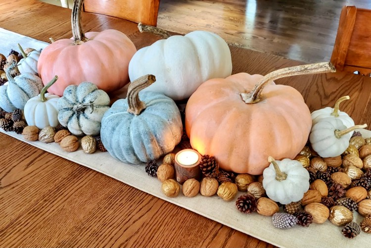 a picture of several  painted pumpkins on the table.  Walnuts, pinecones, tea light candles in wood bark holders