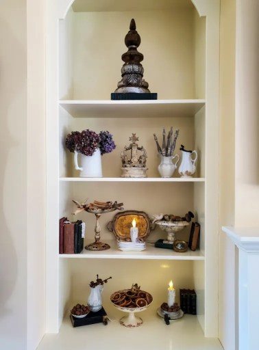 Closer view of fall decor on the bookcase with lit candles
