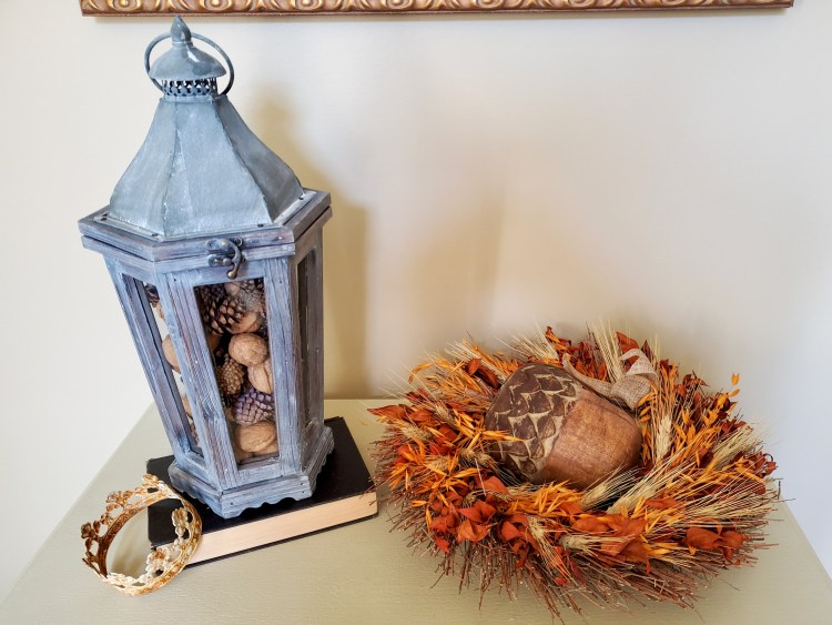 a close up of a lantern filled for natural fall decor  a large wooden acorn inside a wreath laying on the cabinet