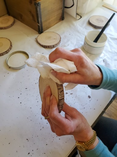 Wiping the  white wax in the bark on the wood coasters
