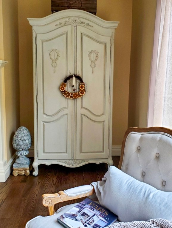 full shot of the French Armoire with the dried citrus wreath and a chair with a book and throw on the chair