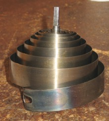 "The original mainspring is ""coned"" instead of being flat. This can happen when someone inserts it into the barrel by hand instead of using a mainspring winder. This is a very severs case of coning - the coned spring is 3 1/4 inches tall!"