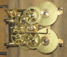 Showing the gears after the movement has been repaired and is ready for assembly. The strike hammer arbor is in place.