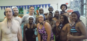 Coach, swimmers, employees get photo taken at the Y with water polo caps.