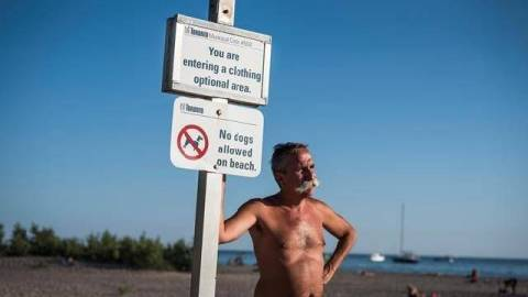 Man at clothing optional beach sign