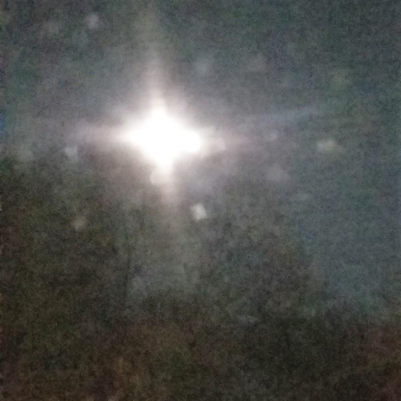 a big april moon through a dirty window at midnight