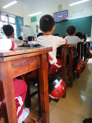 Kids in class with helmets at their sides