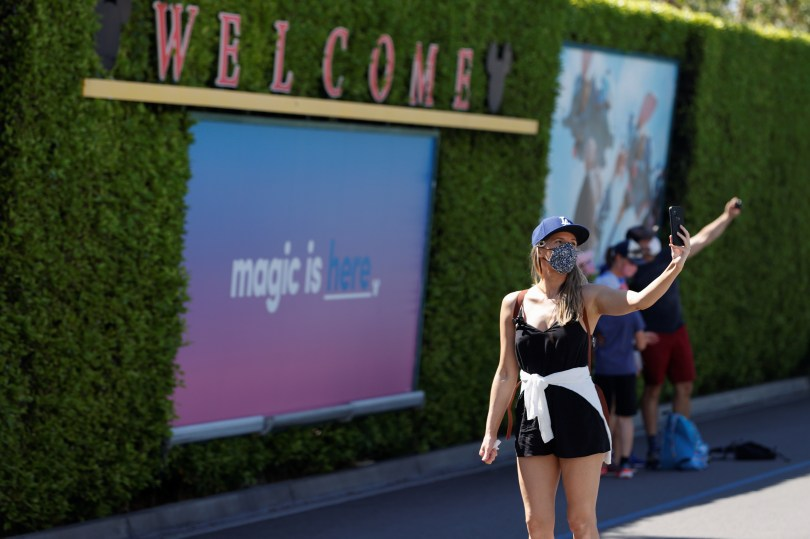 A woman takes a selfie outside Disneyland Park on its reopening day amidst the coronavirus disease (COVID-19) outbreak, in Anaheim, California, U.S., April 30, 2021. REUTERS/Mario Anzuoni