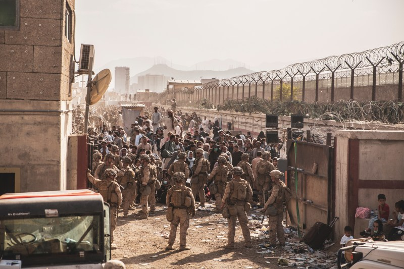 U.S. Marines provide assistance at an Evacuation Control Checkpoint (ECC) during an evacuation at Hamid Karzai International Airport, Afghanistan, August 22, 2021. Picture taken August 22, 2021.  U.S. Marine Corps/Staff Sgt. Victor Mancilla/Handout via REUTERS/Files