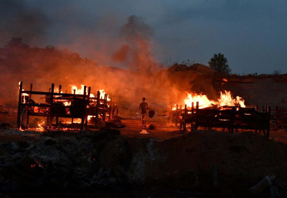A volunteer walks in between burning pyres of persons who died due to the coronavirus disease (COVID-19), at a crematorium ground in Giddenahalli village on the outskirts of Bengaluru, India, May 2, 2021. REUTERS/Samuel Rajkumar