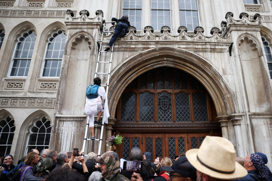 Extinction Rebellion climate activists use a ladder to climb the Guildhall in London, Britain August 22, 2021. REUTERS/Henry Nicholls