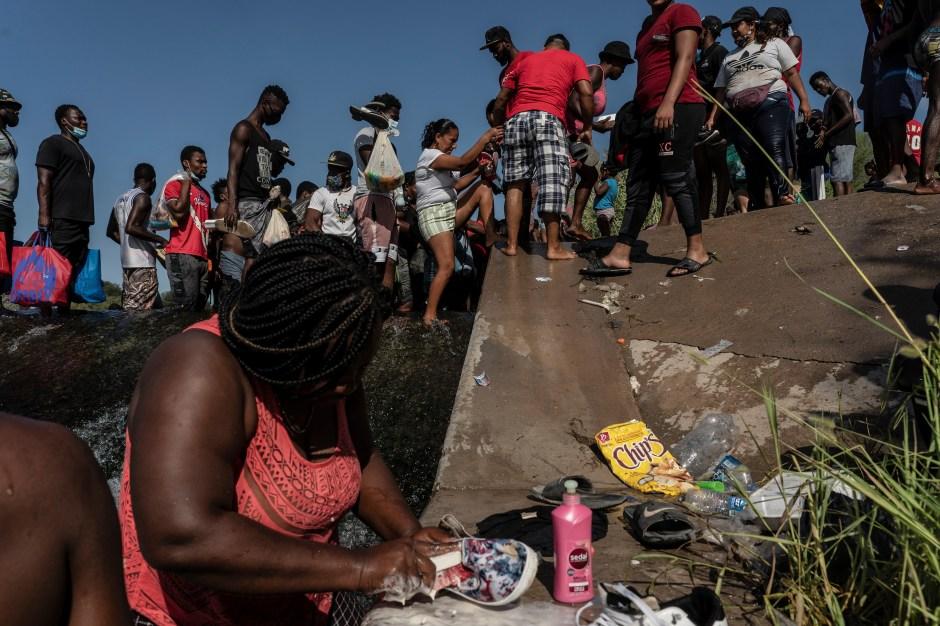Migrantes que buscan asilo en los EE. UU. Caminan por el río Grande cerca del Puente Internacional entre México y EE. UU., Mientras esperan ser procesados, en Del Rio, Texas, EE. UU., El 16 de septiembre de 2021. Según funcionarios, algunos migrantes cruzan de regreso y luego a México para comprar alimentos y suministros.  REUTERS / Go Nakamura
