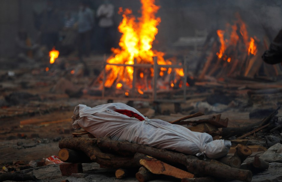 The body of a person, who died from the coronavirus disease (COVID-19), lies on a funeral pyre during a mass cremation, at a crematorium in New Delhi, India May 1, 2021. REUTERS/Adnan Abidi