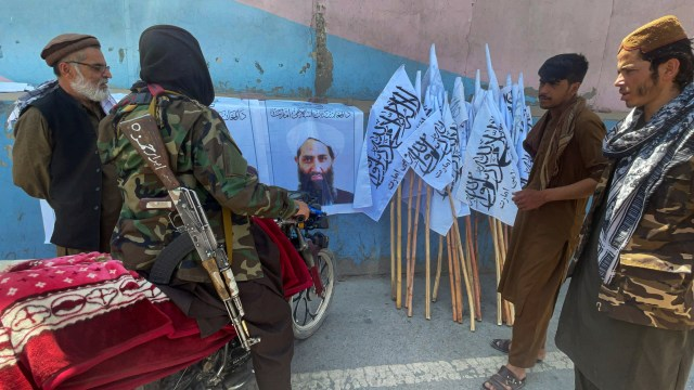 Members of Taliban forces gather and look at the picture of their leader Mullah Haibatullah Akhundzada, in Kabul, Afghanistan August 25, 2021. Picture taken August 25, 2021. REUTERS/Stringer