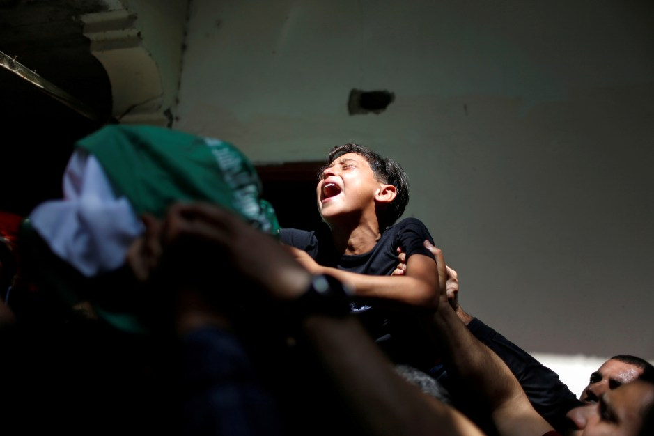 The brother of Palestinian man Ahmed Al-Shenbari, who was killed amid a flare-up of Israeli-Palestinian violence, reacts as mourners carry his body during his funeral in the northern Gaza Strip May 11, 2021. REUTERS/Mohammed Salem     TPX IMAGES OF THE DAY