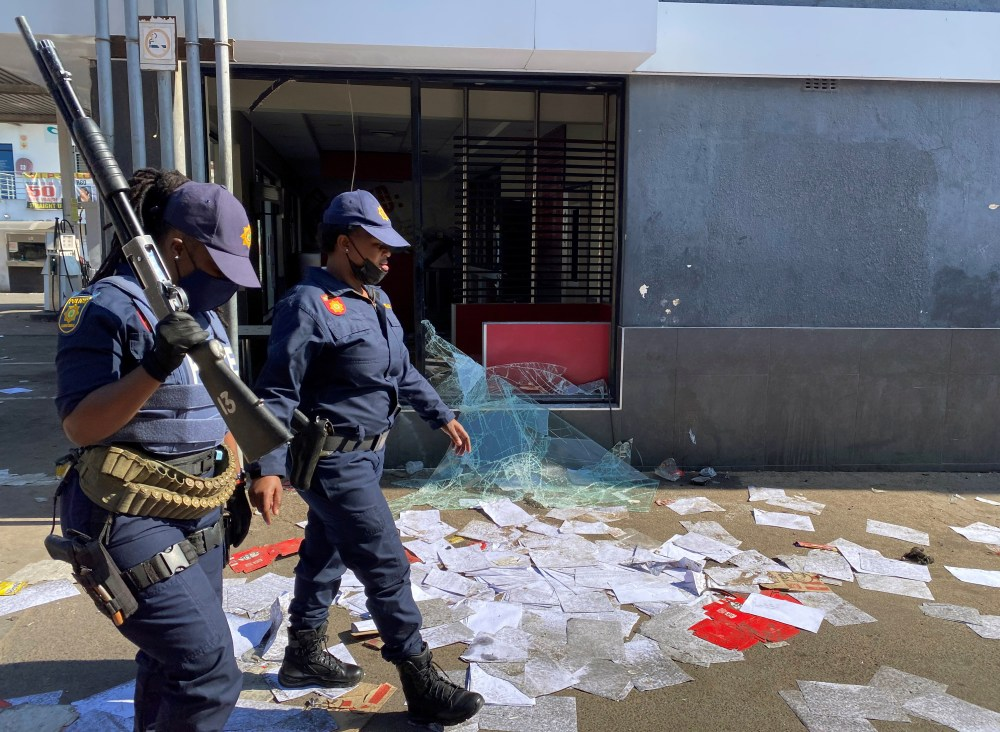 Police walk past a shop looted in protests following the jailing of former South African President Jacob Zuma,  in Durban, South Africa, July 11, 2021. REUTERS/Siyabonga Sishi