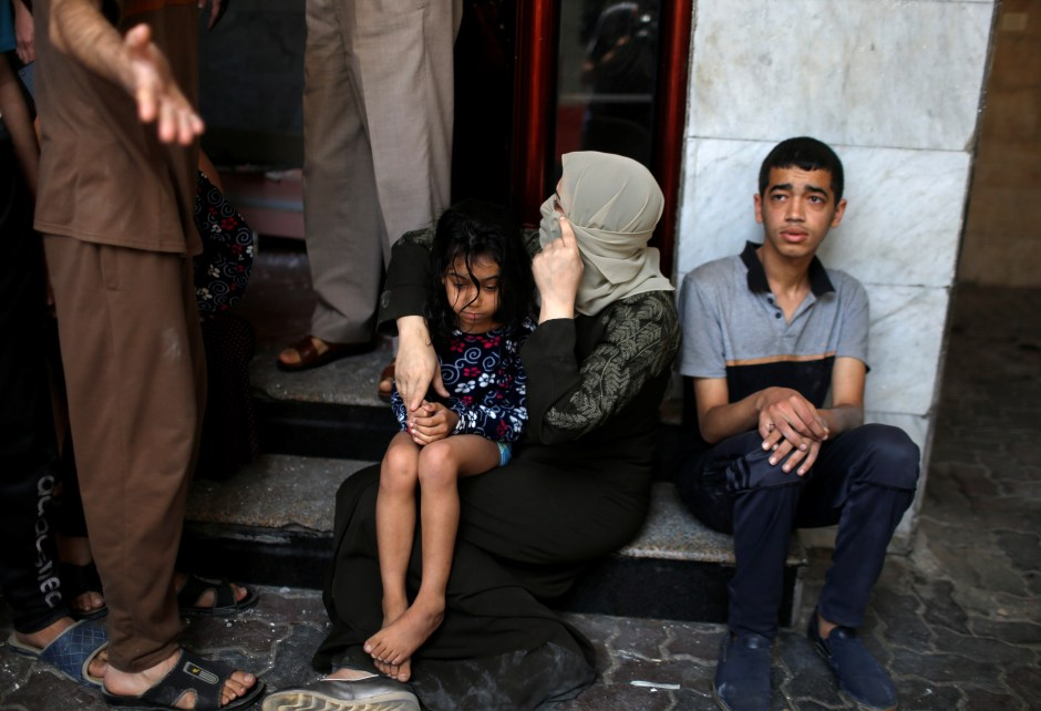 Palestinians sit as they evacuate following an Israeli air strike on a building, amid a flare-up of Israeli-Palestinian violence, in Gaza City May 11, 2021. REUTERS/Mohammed Salem