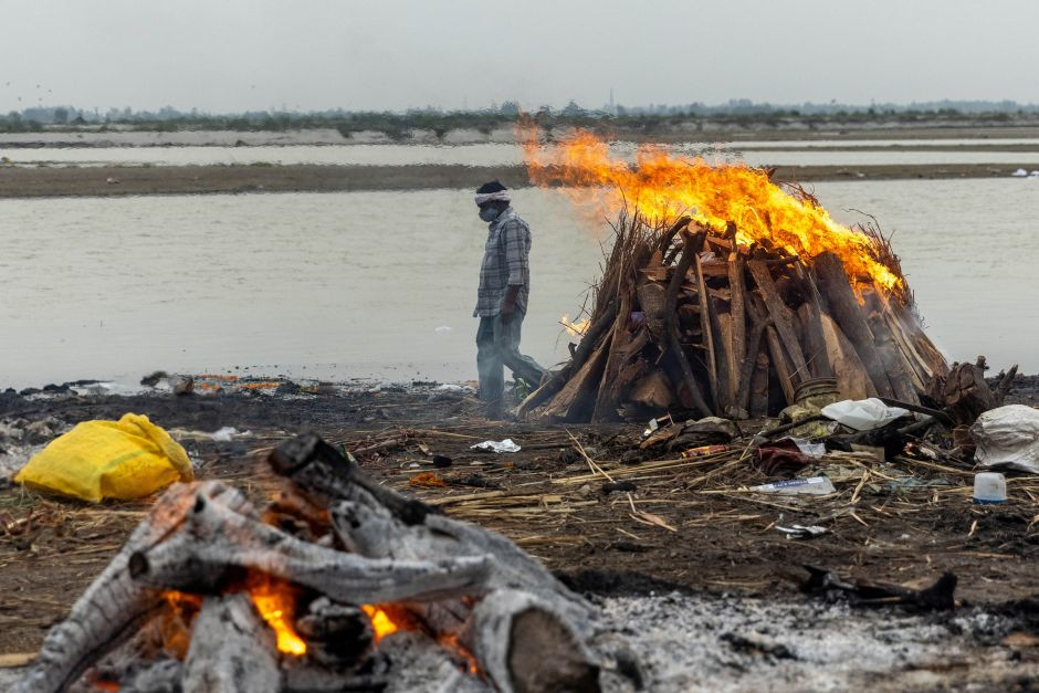A man walks past burning pyres with people who died from the coronavirus disease (COVID-19), on the banks of the river Ganges at Garhmukteshwar in the northern state of Uttar Pradesh, India, May 6, 2021. REUTERS/Danish Siddiqui