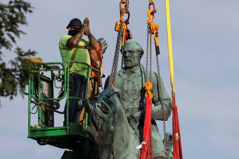 A worker gesture as he removes a statue of Confederate General Robert E. Lee, after years of a legal battle over the contentious monument, in Charlottesville, Virginia, the U.S, July 10, 2021. REUTERS/Evelyn Hockstein