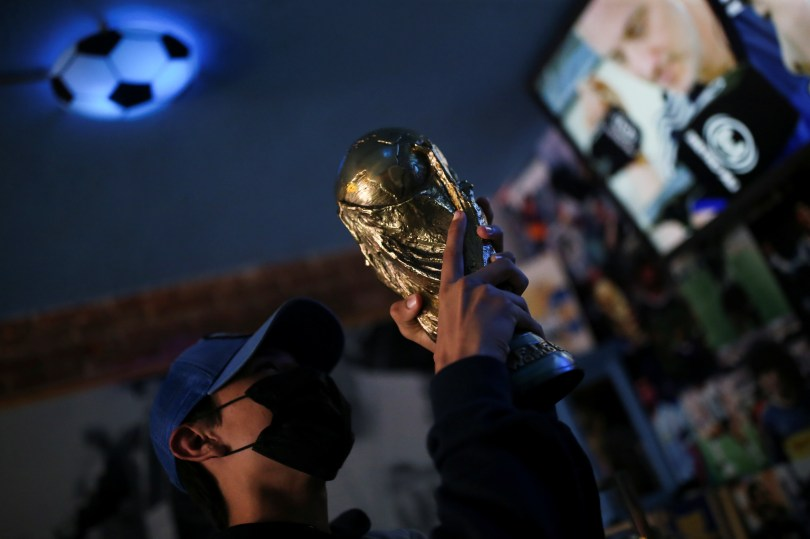 A fan holds up a replica of the World Cup trophy at the first Mexico's church in memory of soccer legend Diego Armando Maradona in San Andres Cholula, in Puebla state, Mexico July 14, 2021. REUTERS/Edgard Garrido