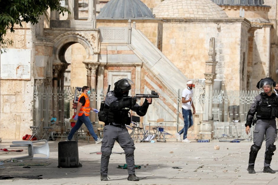 A member of Israeli police aims a weapon during clashes with Palestinians at the compound that houses Al-Aqsa Mosque, known to Muslims as Noble Sanctuary and to Jews as Temple Mount, in Jerusalem's Old City, May 10, 2021. REUTERS/Ammar Awad