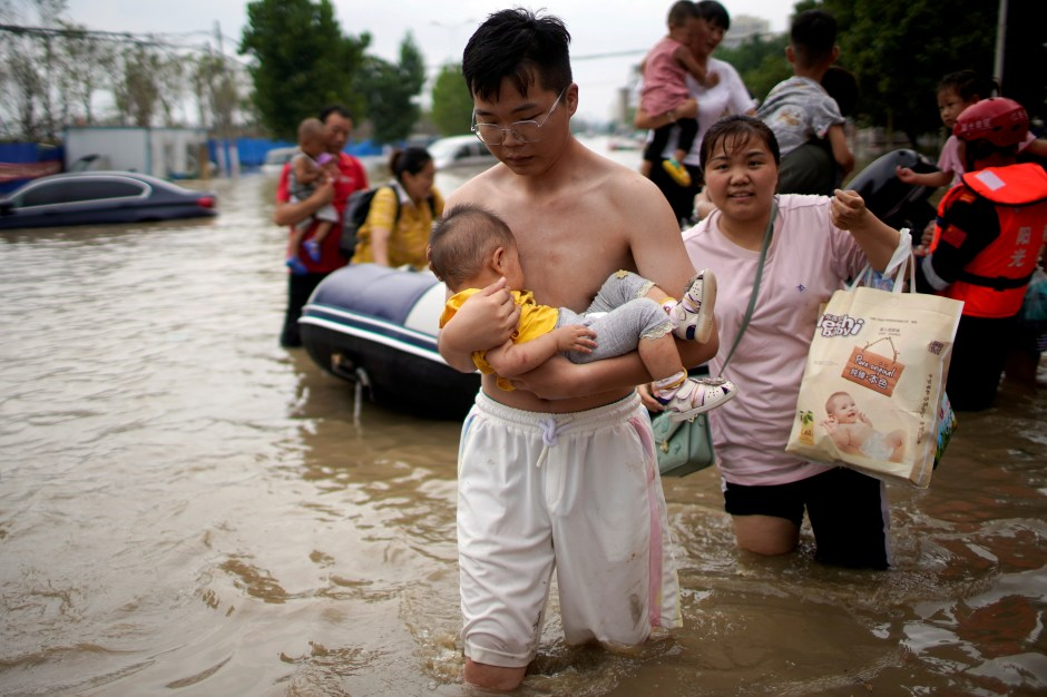 A man holding a baby wades through a flooded road following heavy rainfall in Zhengzhou, Henan province, China July 22, 2021.  REUTERS/Aly Song/File Photo