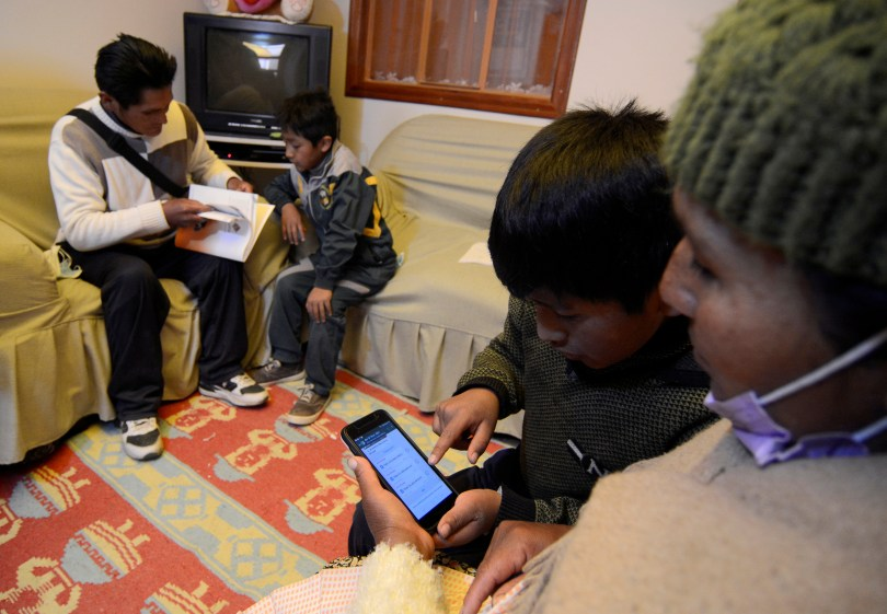 Carlos Gutierrez and his mother Angela Poma look at a smartphone after learning how to use it for virtual home schooling, during the coronavirus disease (COVID-19) outbreak, in El Alto, Bolivia July 12, 2021. Picture taken July 12, 2021. REUTERS/Claudia Morales