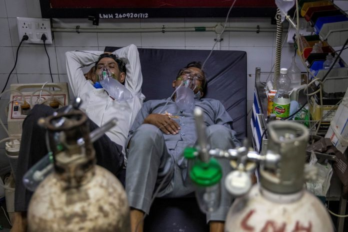 Two to a bed in Delhi hospital as India's COVID crisis spirals | Reuters