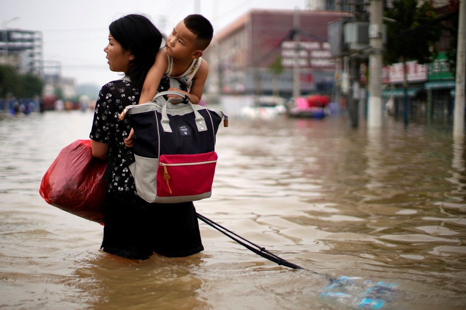 A woman carrying a child and belongings wades through floodwaters following heavy rainfall in Zhengzhou, Henan province, China July 23, 2021. REUTERS/Aly Song