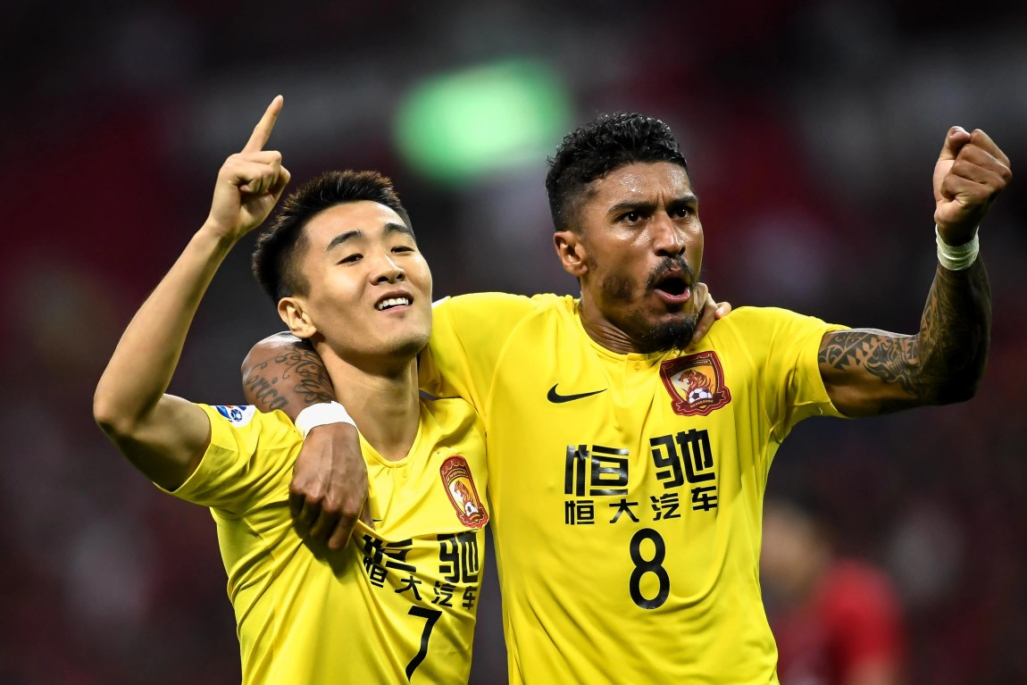 Chinese football player Wei Shihao of Guangzhou Evergrande Taobao F.C., left, and Brazilian football player Paulinho of Guangzhou Evergrande Taobao F.C., right, celebrates a goal which will be denied soon during the first-round match of AFC Champions League (ACL) against Urawa Red Diamonds