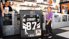 A child holding up a framed jersey of Sidney Crosby on National Hockey Card Day 2019