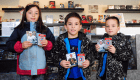 A group of 3 children holding up a pack of hockey cards for National Hockey Card Day 2019