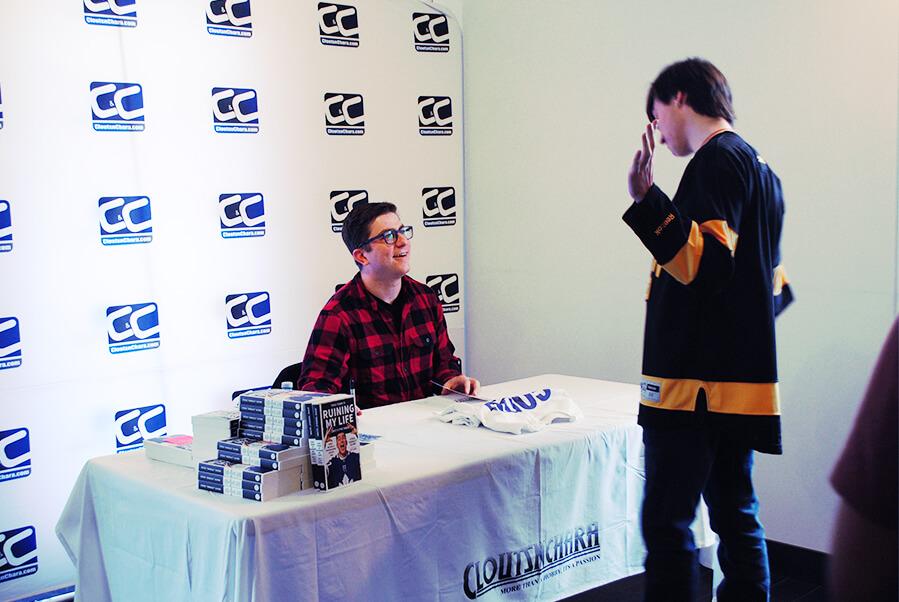 Steve Dangle Glynn talking to a fan wearing a Boston Bruins jersey.