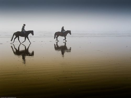 Two equestrian riders, girls on horseback, in low tide reflections on serene Morro Strand State Beach, por mikebaird