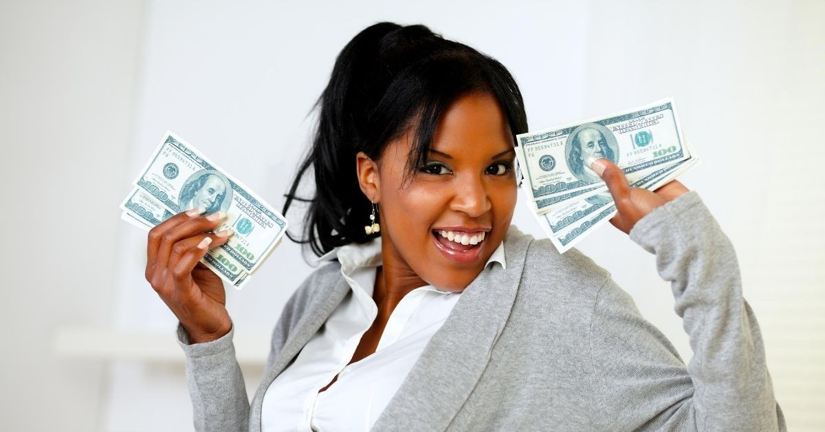 Why Saving Money Feels as Good as Spending Does - picture of woman smiling and holding up cash