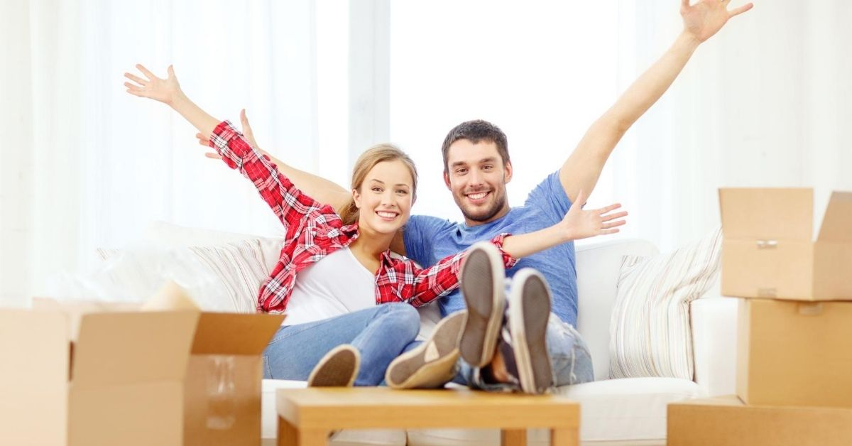 Mortgage Prepayment Money in the Bank - picture of young couple hands raised among moving boxes