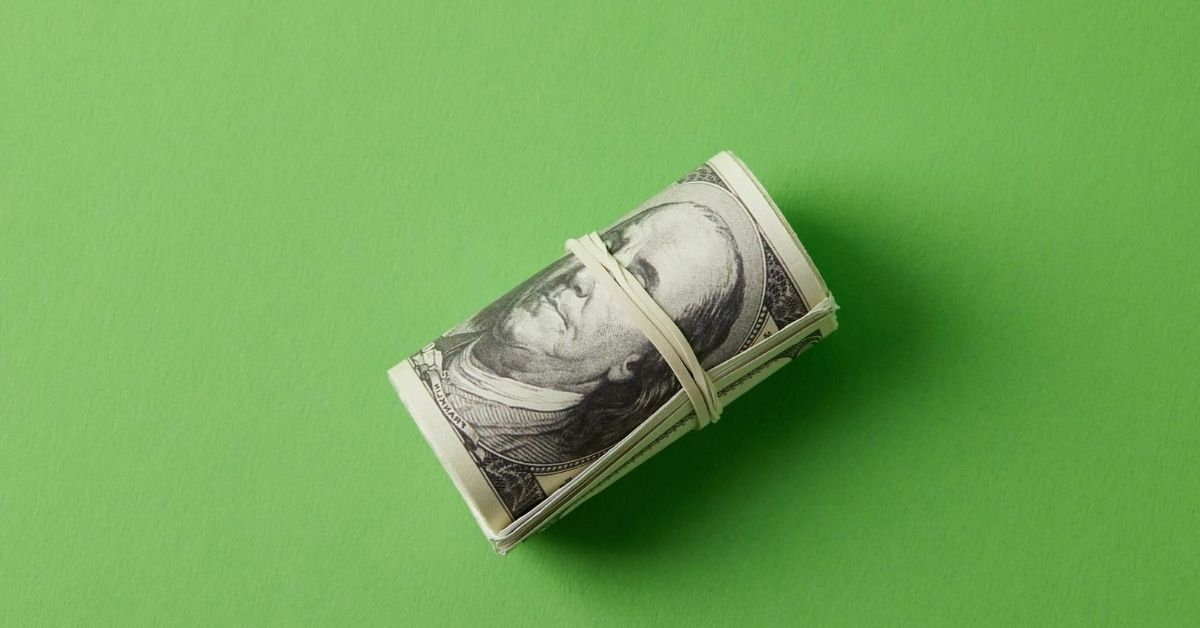 3 Big Mistakes Couples Make With Money - picture of roll of bills secured with rubberband on green background